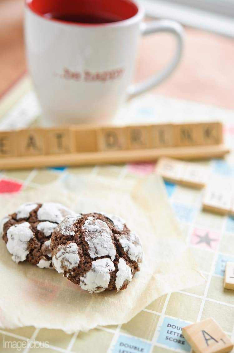 "Close up of Chocolate-Mint Crackle Cookies on a scrabble board. Words ""Eat drink"" are visible in the background. Cup is in the background"