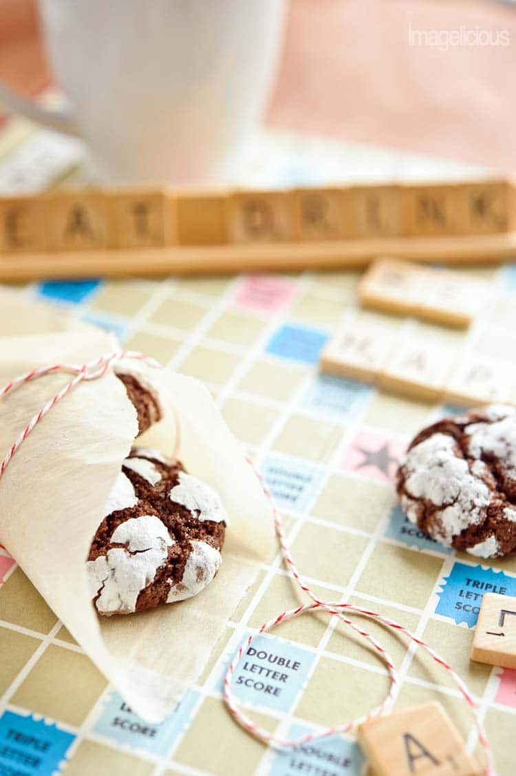 "Another close up of Chocolate-Mint Crackle Cookies, wrapped in parchment paper with festive red string. All on a scrabble board with words ""eat drink"" blurry in the background"