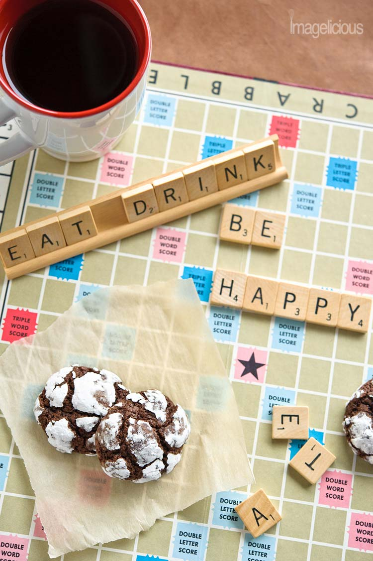 "Scrabble board with a mug of coffee, words ""eat drink and be happy"" and two Chocolate-Mint Crackle Cookies"