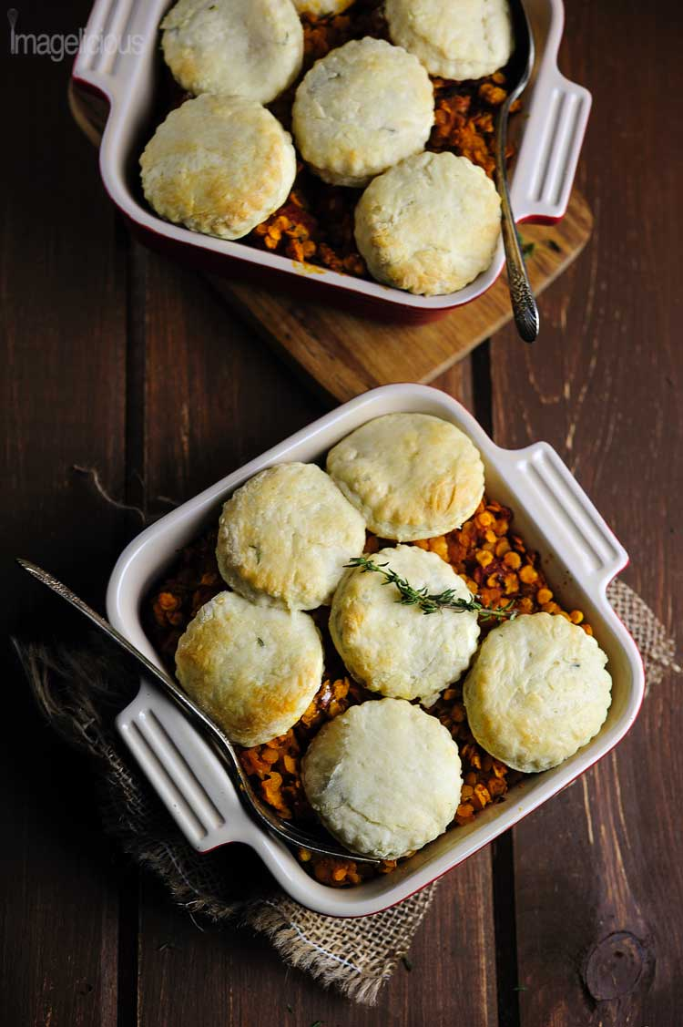 Dark/low key photography. Top down view of two dishes filled with lentil stew and topped with biscuits