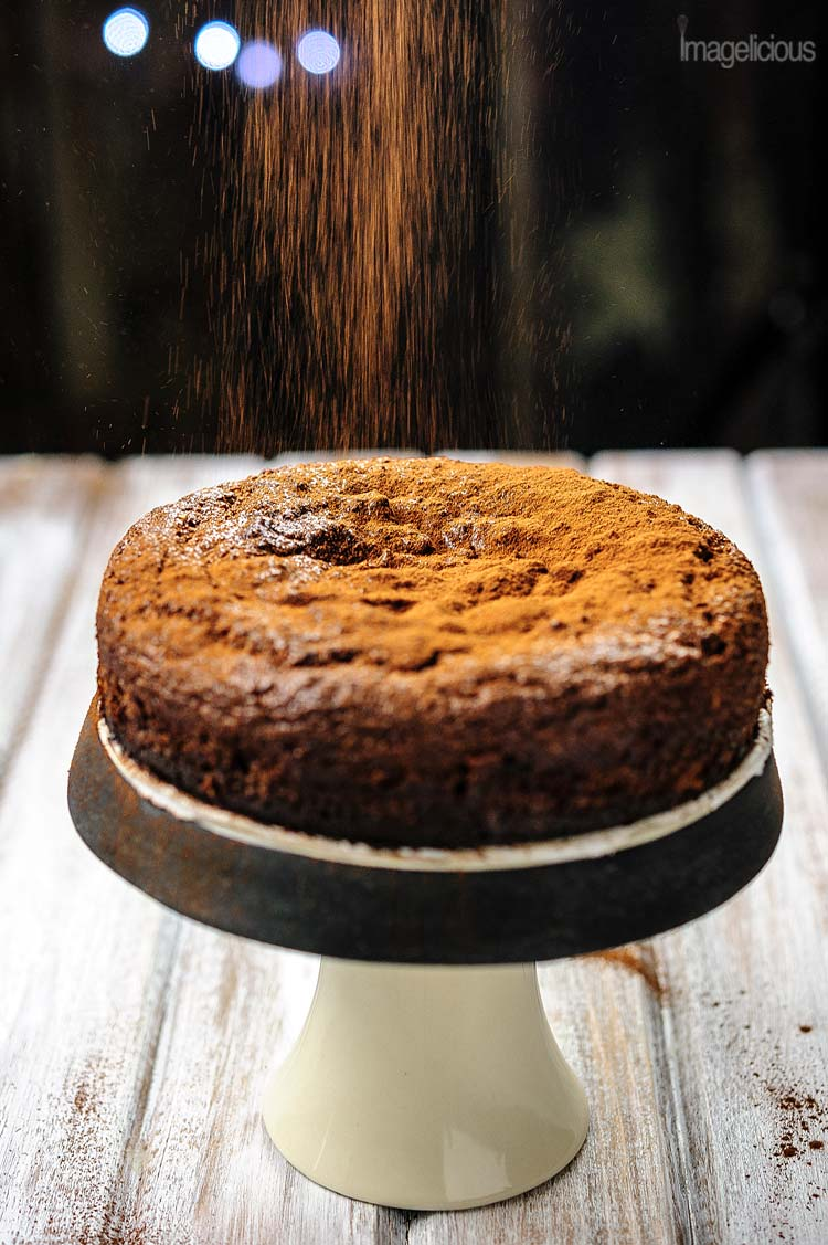 Small cake stand with a Gluten-Free Almond Ricotta Chocolate Cake and a dusting of cocoa powder falling on top of it