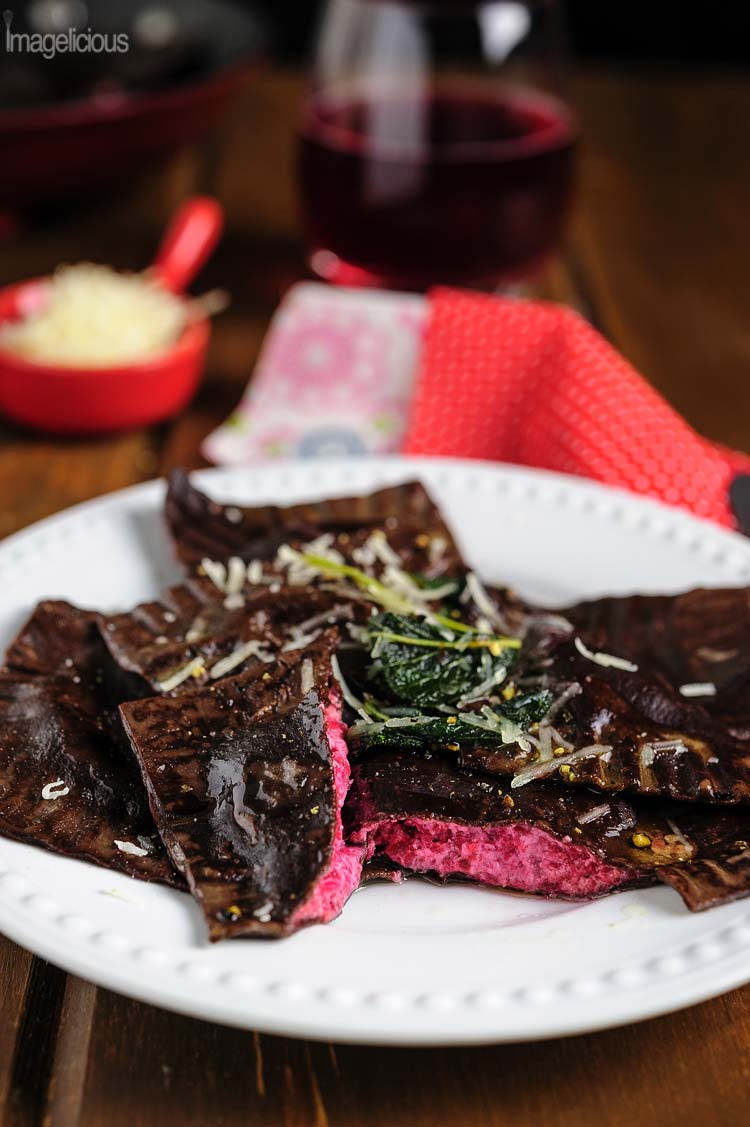 Close up of a plate with chocolate ravioli and one of them is cut in half so that beautiful pink Ricotta-Beet filling is visible